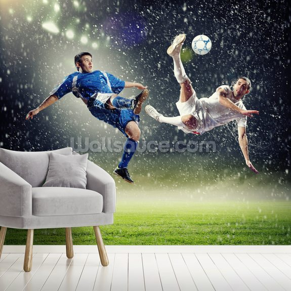 . Two football players striking the ball