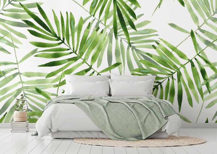 white and green leaf print wallpaper behind white bed