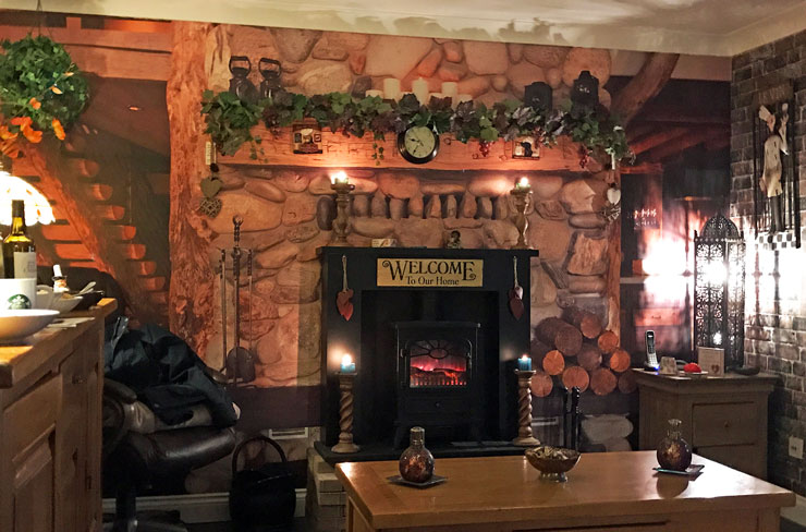 cosy lounge with pretend chimney breast in a log cabin wallpaper