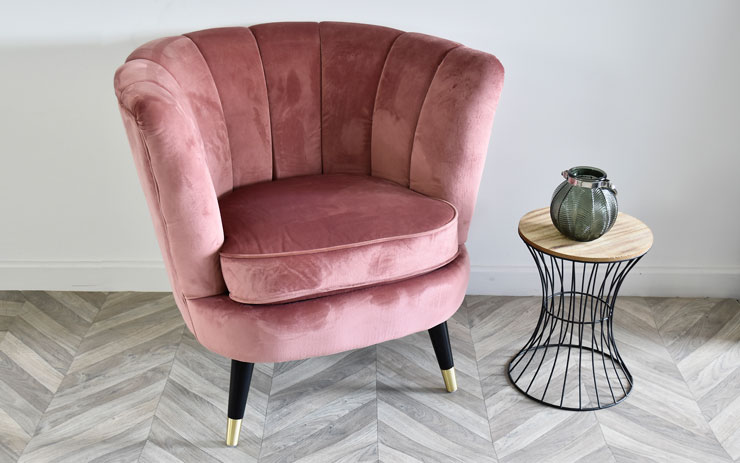 velvet scalloped pink tub chair with small table next to it
