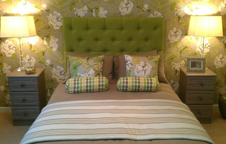 floral green bed with symmetrical bedside tables and lamps
