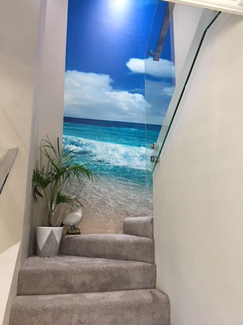 sunny tropical waves wall mural on stylish grey and white staicase