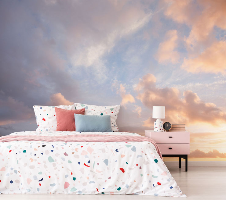 blue sky and pink sunset clouds wall mural in bedroom with terrazzo pastel duvet covers