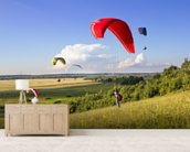 Multiple paragliders soar in the air amid wondrous landscape wallpaper mural living room preview