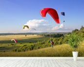 Multiple paragliders soar in the air amid wondrous landscape wallpaper mural in-room view