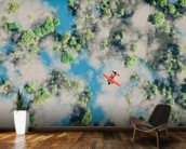 Aerial of red airplane flying over forest wall mural kitchen preview