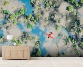 Aerial of red airplane flying over forest wall mural living room preview