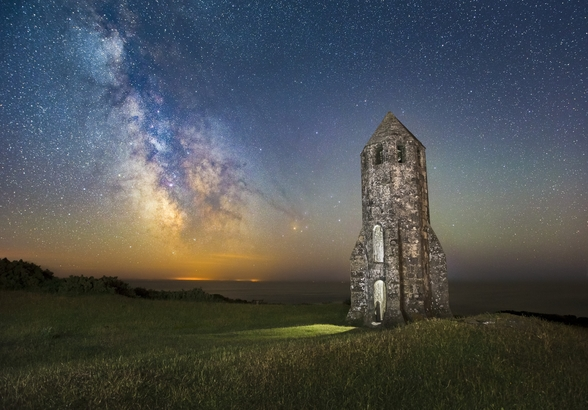 Medieval lighthouse next to The Milky Way wall mural