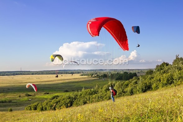 Multiple paragliders soar in the air amid wondrous landscape wallpaper mural