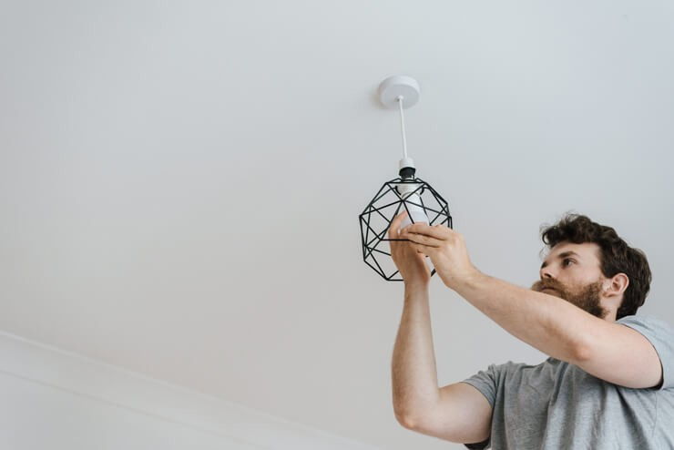 brown haired man with beard changing a ceiling bulb