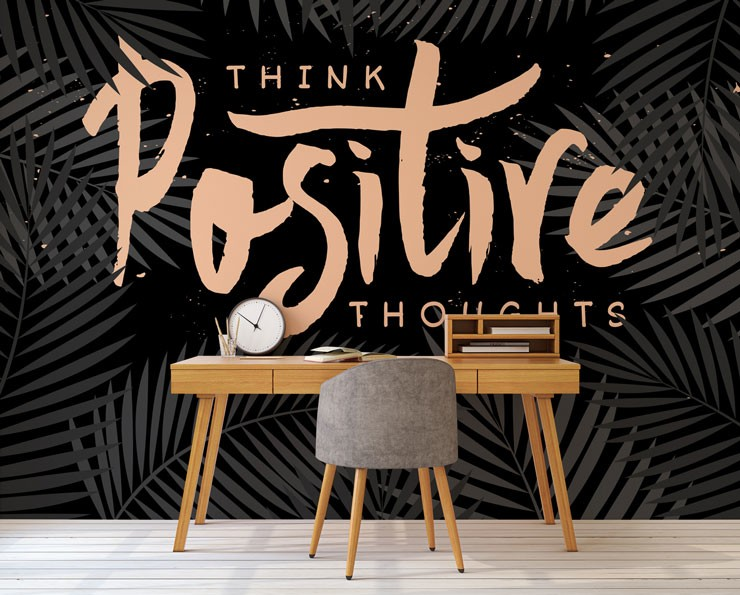 black wallpaper with pink writing that says 'think positive thoughts' in home office with wooden desk and grey chair