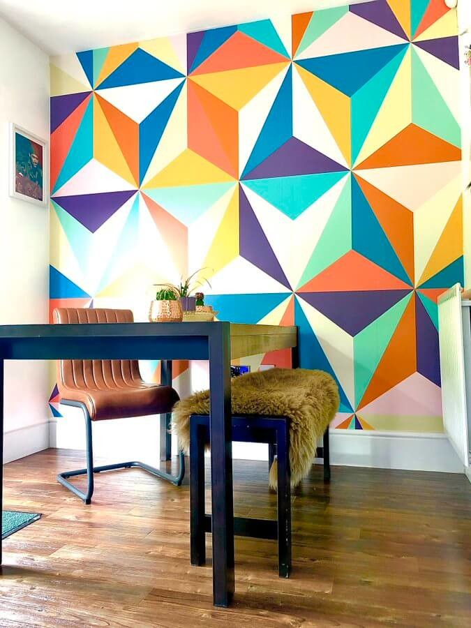 multicoloured geometric triangle wallpaper in retro 70s style room with wooden desk and fur covered bench