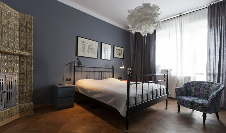 blue bedroom with metal bed and soft furnishings
