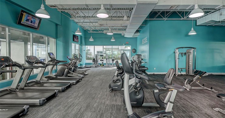 large gym with teal walls and vast equipment
