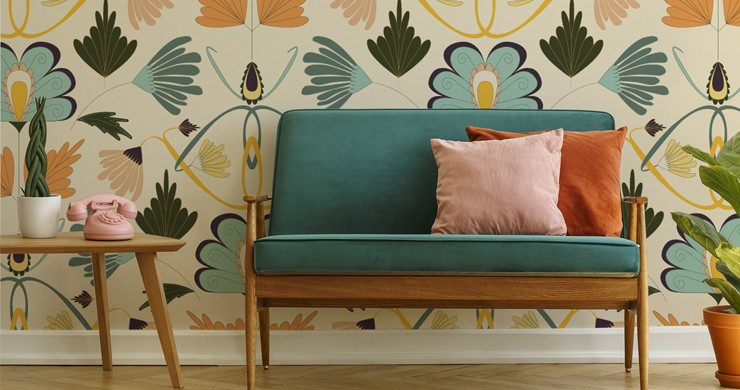 teal green sofa with pink and orange cushions with art nouveau feature wall