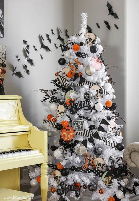 white christmas tree with black and orange halloween decorations