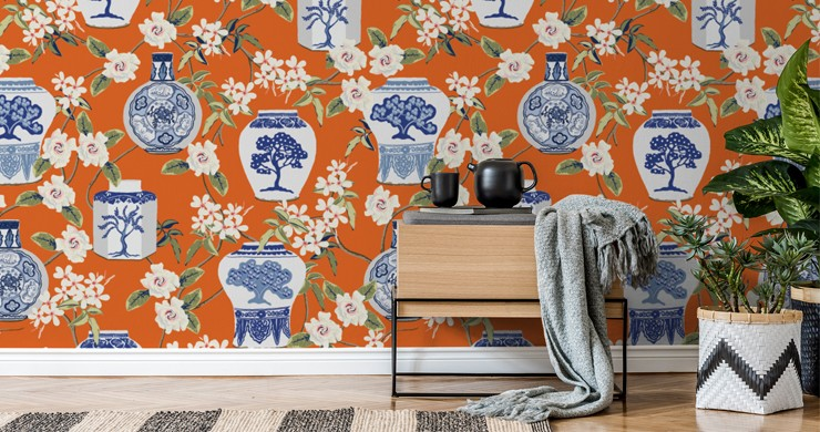 blue and white oriental pottery on an orange background wallpaper in cosy lounge with table, tea pot and blanket