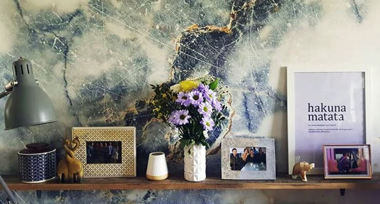 blue and white marble effect wallpaper behind floating shelves with flowers and photos