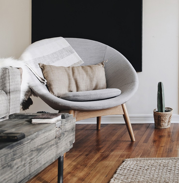round styled grey chair with black canvas painting behind it
