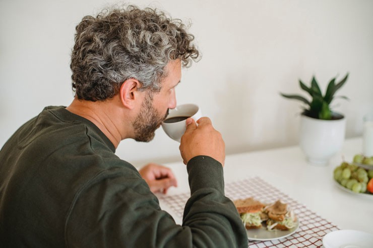 man with grey hair sat at table drinking coffee and eating a sandwich