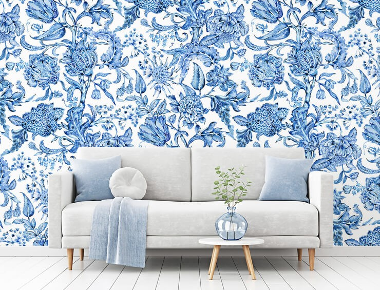 blue and white floral wallpaper in living room with off white sofa with blue cushions