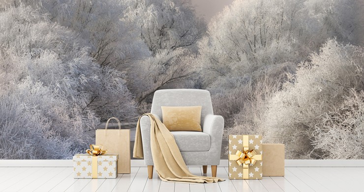 frosty white trees by a river wallpaper in room with silver armchair with gold coloured cushion and christmas presents