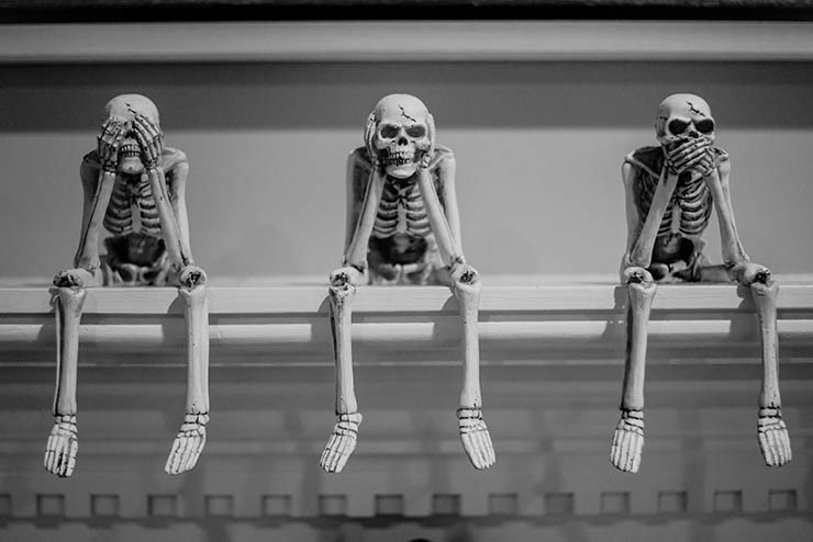 three mini skeletons hanging from a mantel
