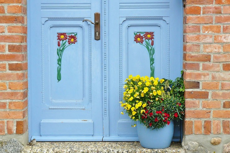 aqua blue door with colourful floral detail with potted plant and small bird on step