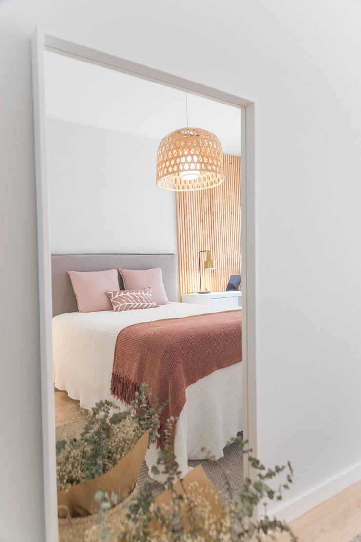 door view of pink and white bedroom with wicker lampshade
