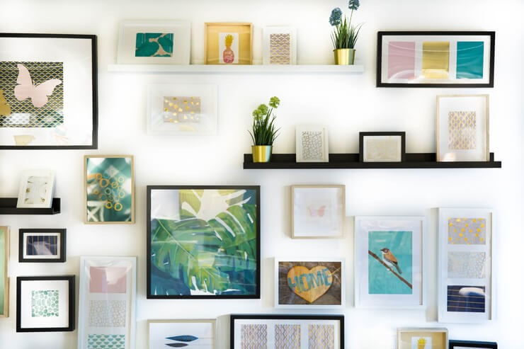 pastel pink, yellow and blue prints framed on wall in black and white frames