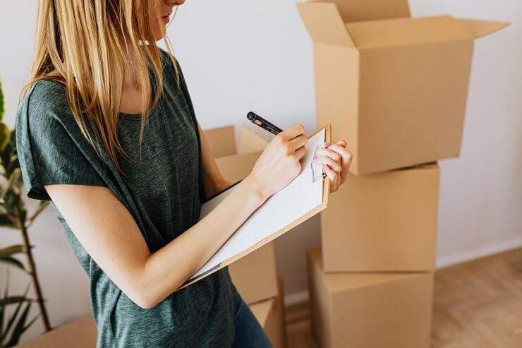 blond woman writing a list whilst moving house