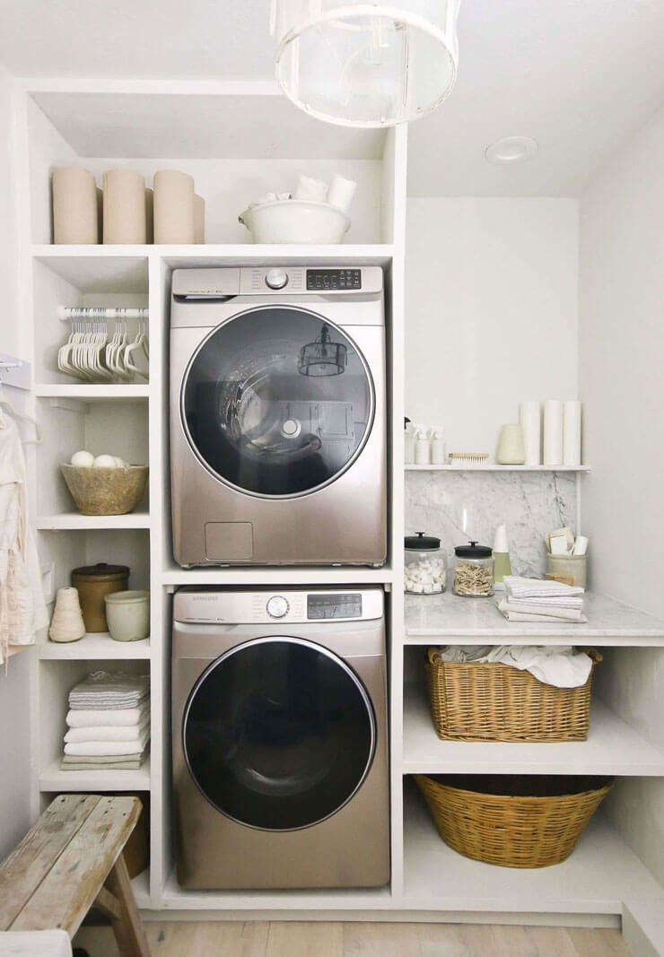 monochrome washer and dryer stacked in cream laundry room