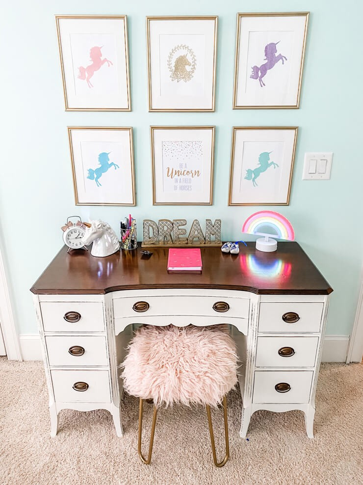 unicorn white desk with framed unicorn prints on wall and pink furry stool