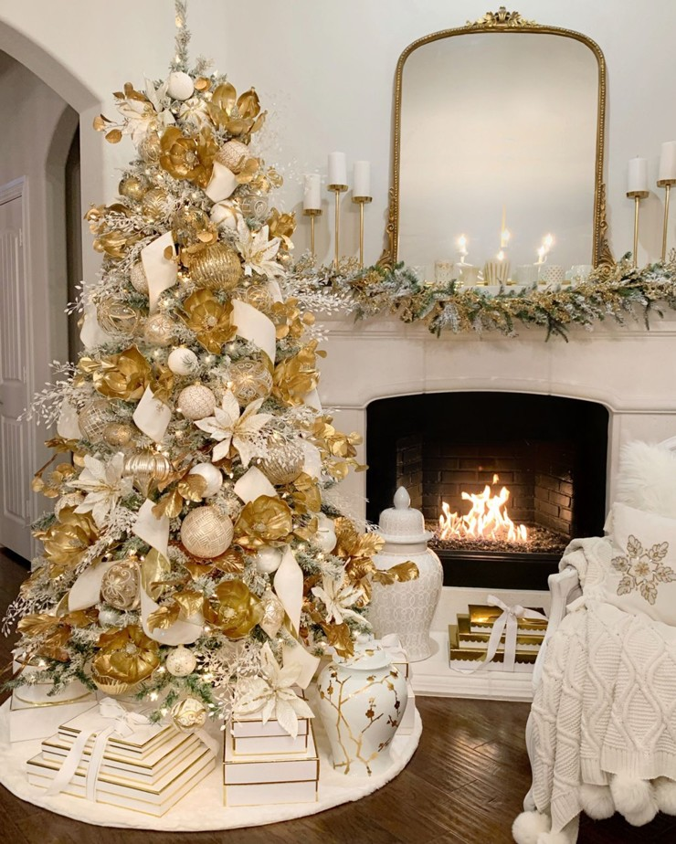 elegant Christmas tree with gold and white decorations, stood by the fireplace