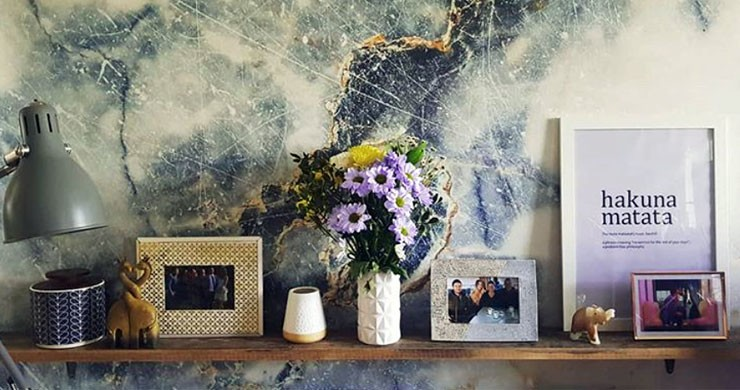blue and white marble effect wallpaper behind shelf with flowers and ornaments on