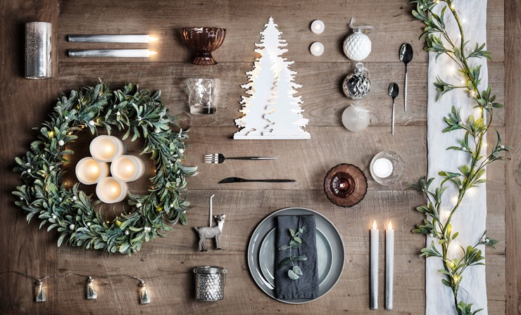 rustic wooden table with mistletoe wreath and simple scandi christmas dinner set