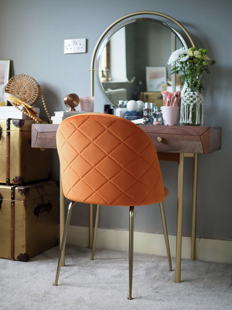gold and wood vanity with round mirror with velvet orange chair