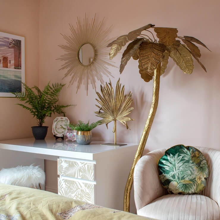 tall golden palm tree sculpture, golden sunburst mirror in pink bedroom