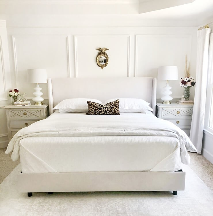 white panelled wall bedroom with white bed and bedside cabinets