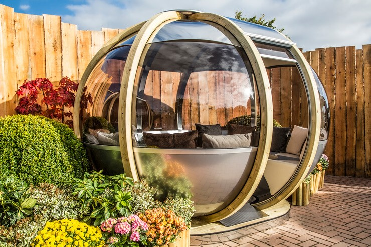 wood and glass round summer house with beautiful summer garden