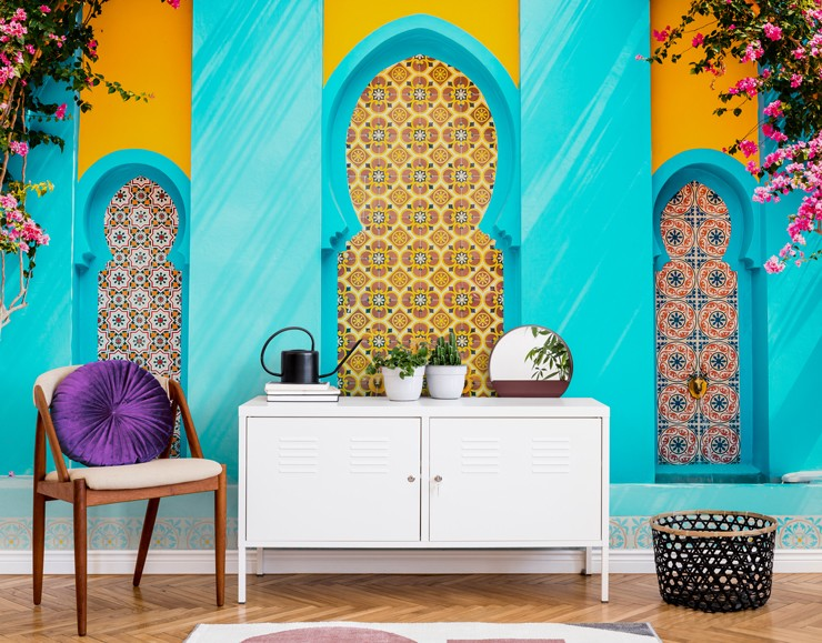 orange and blue photograph of Moroccan building with colorful tiles wallpaper in living room with white cabinet and chair with purple round cushion
