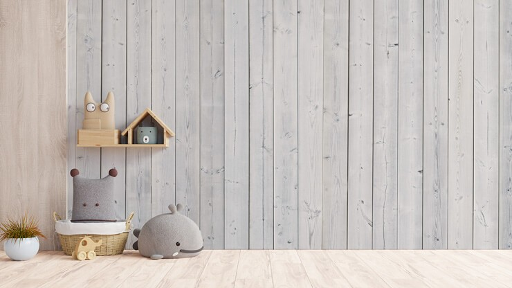 off-white panel effect wallpaper in nursery with grey and wooden toys