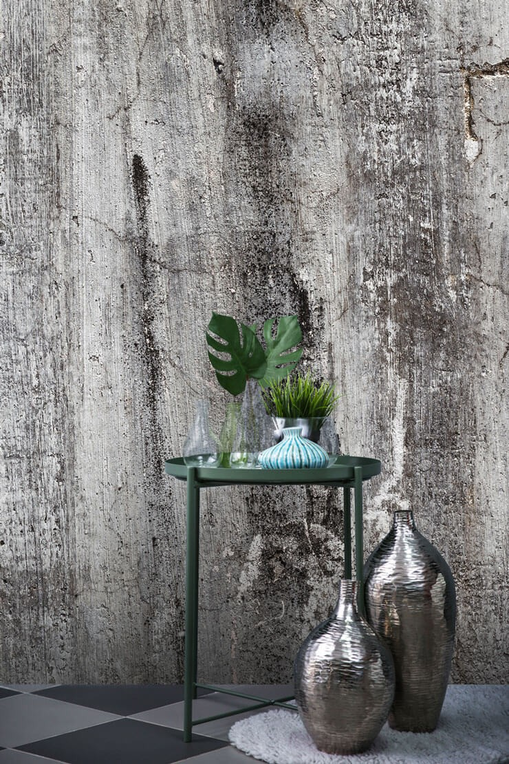 grey and black concrete effect wallpaper with green and silver room accessories