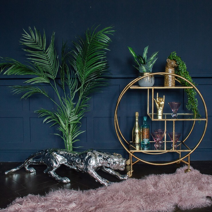 monochrome jaguar ornament, round golden floor shelf and tropical plant in navy room