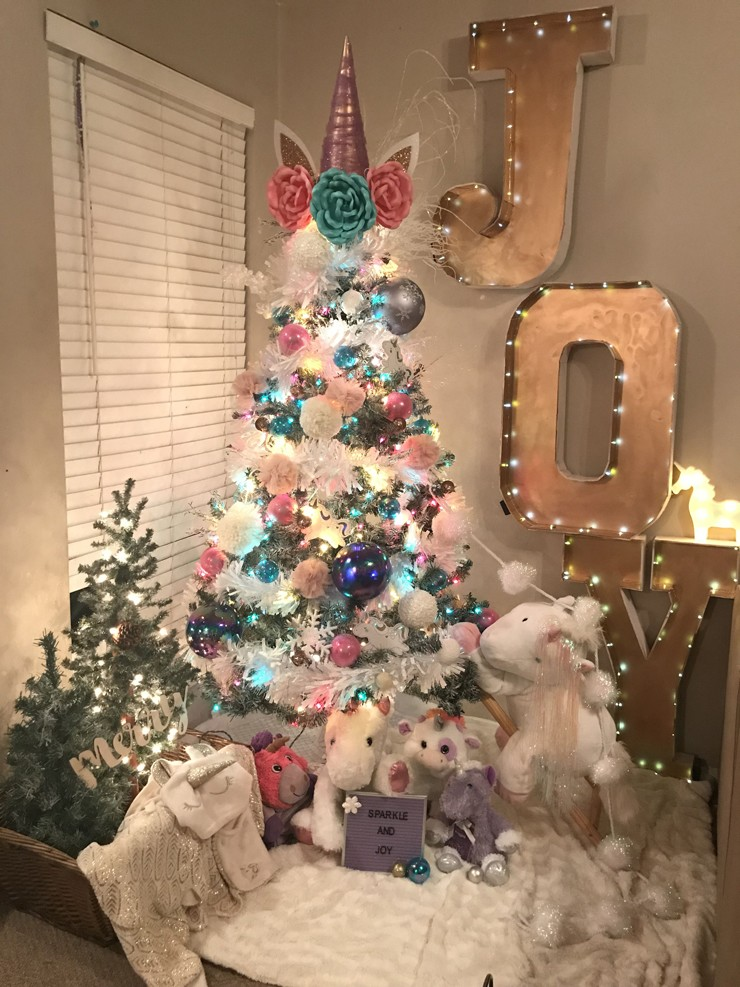 christmas tree covered and surrounded by white and pink unicorn decorations