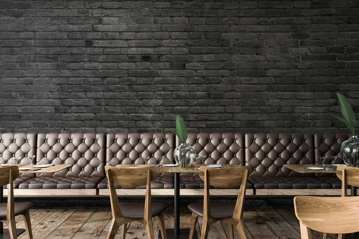 painted black bricks wallpaper in restaurant with leather studded chairs and wooden tables