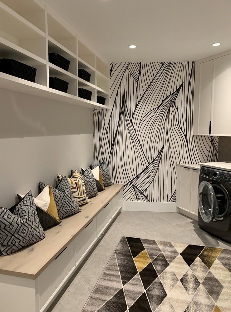 black and gold themed laundry room with black and white leaf illustration wallpaper