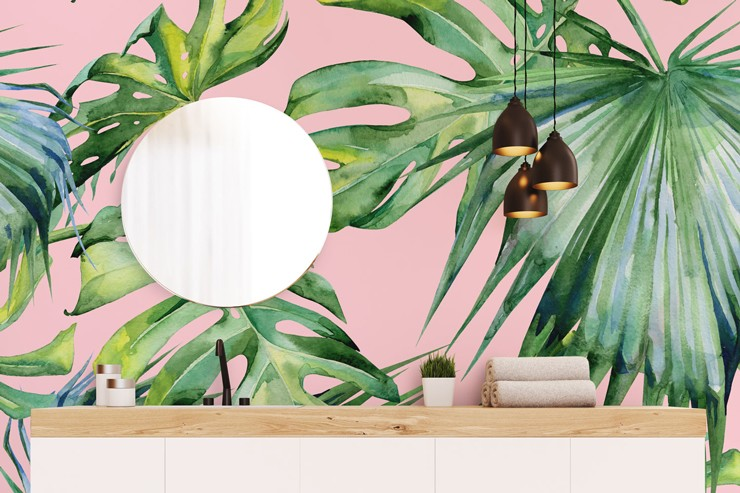 pink wallpaper with green tropical leaves on wall behind round glass mirror in bathroom