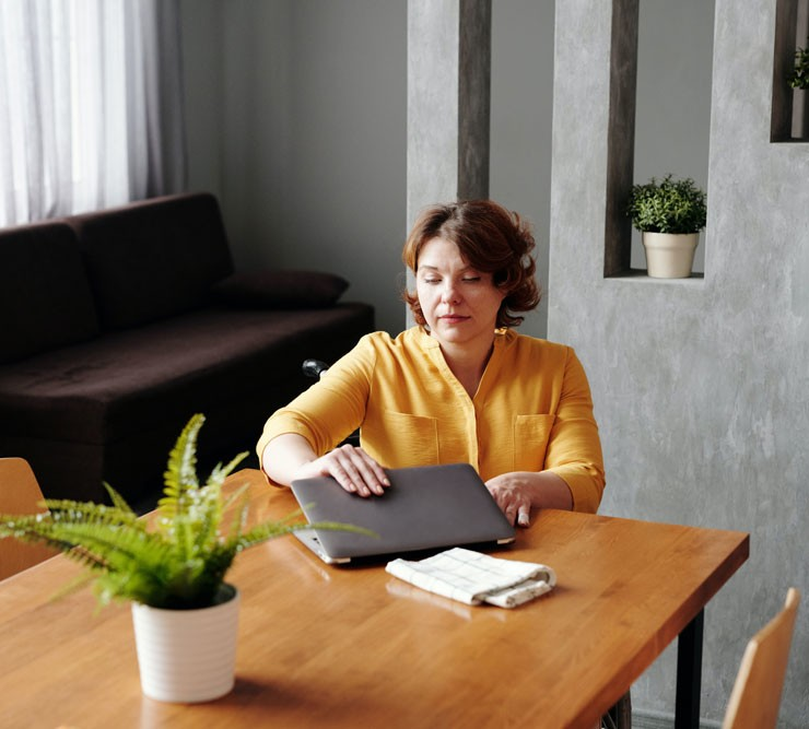 woman with yellow shirt putting away her laptop when the working day is over
