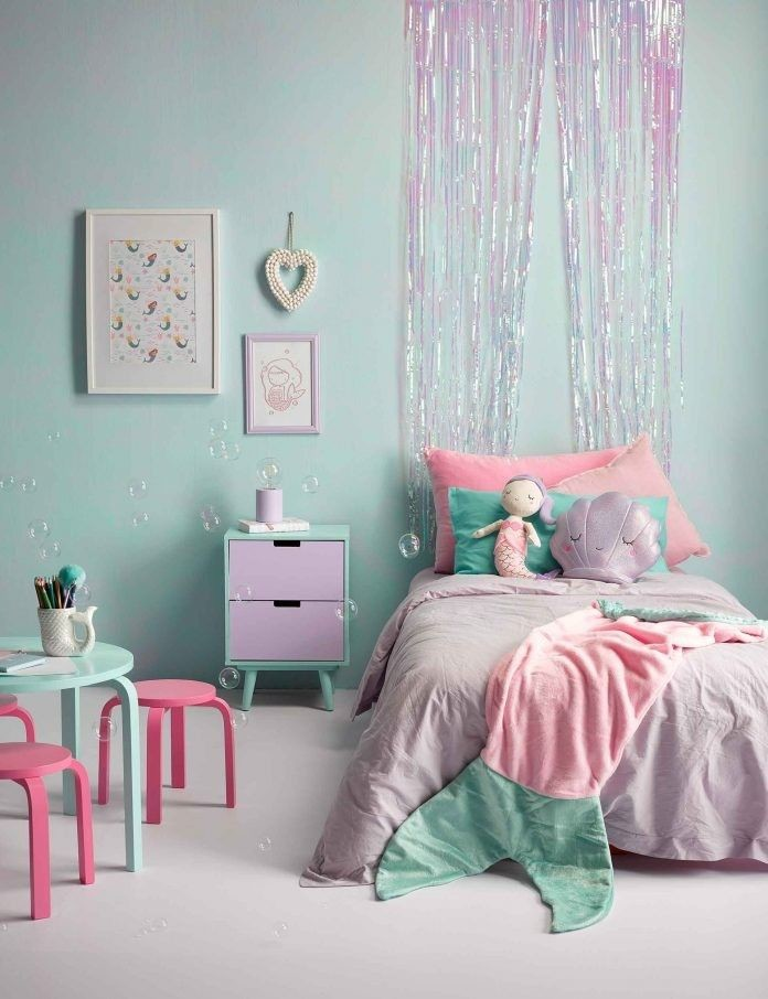 pastel pink and purple child's mermaid bedroom with sparkly tinsel curtain above bed